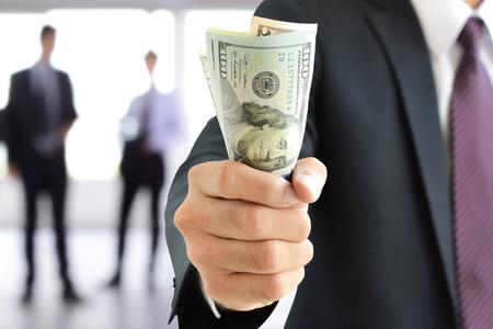 pieniądze: Biznesmen strony trzymania pieniędzy, Dolar amerykański (USD) weksle - inwestycje, sukces i zyskownych koncepcji biznesowych Zdjęcie Seryjne