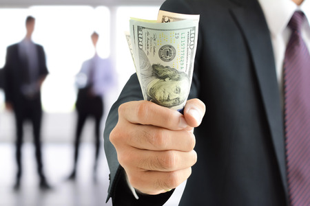 Businessman hand gripping money, US dollar (USD) bills - investment, success and profitable business concepts