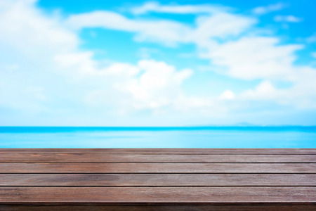 Old brown wood table top on blur sea and summer sky background - can be used for display and montage your products