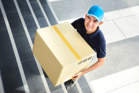 deliveryman: Deliveryman walking up stairs, carrying a big parcel box