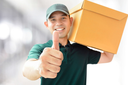 Great: Deliveryman carrying a parcel box, giving thumbs up