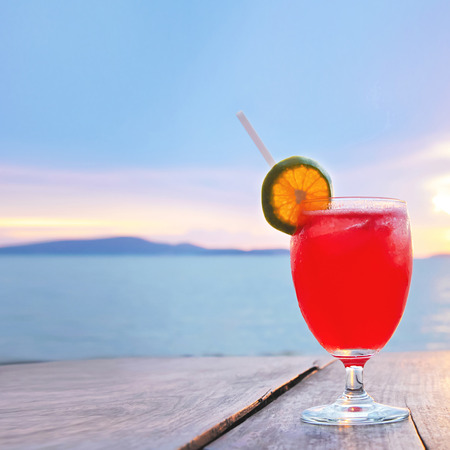cocteles: Bebida roja del coctel en la mesa de madera en el crepúsculo del mar y el cielo de fondo