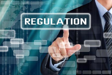 Businessman hand touching REGULATION  sign on virtual screen Standard-Bild