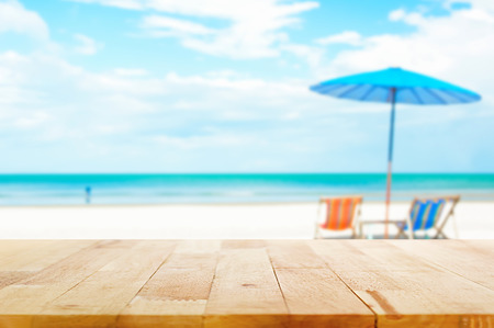 tabla de madera: Vector de madera en el fondo de la playa de desenfoque con sillas de playa y sombrilla - se puede utilizar para la visualización o el montaje de sus productos