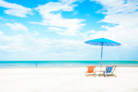 parasols: Blurred image of beach chairs and parasol on white sand beach in summer blue sky background