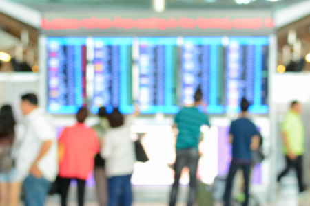 terminals: Blur image of people looking at airport timetable screens in airport terminal Stock Photo