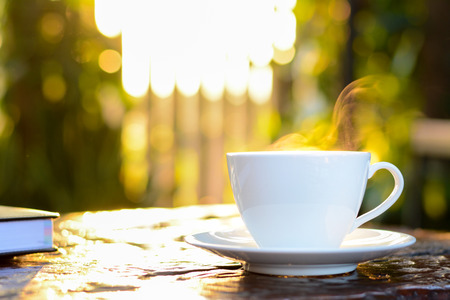 decaffeinated: Hot coffee in the cup on old wood table with blur natural green background - soft focus