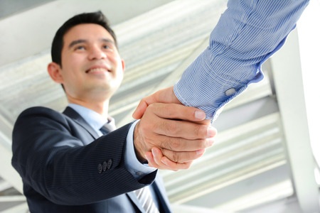 acquisition: Businessmen making handshake with smiling face - greeting, dealing, merger and acquisition concepts