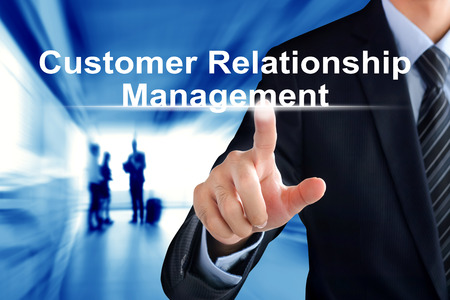 relationship strategy: Businessman hands touching Customer Relationship Management (or CRM) sign on virtual screen