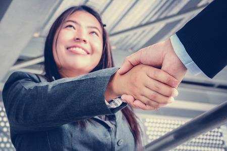 Lachend zakenvrouw maken handdruk met een zakenman Stockfoto