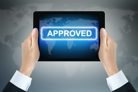 approved sign: APPROVED sign on tablet pc screen held by businessman hands