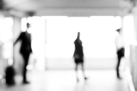 blurred people: Blurred business people standing in building hall, monochrome effect - modern business background concept Stock Photo