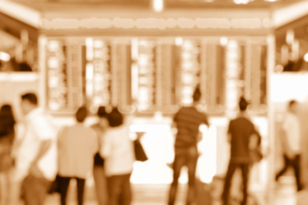 blur effect: Blur image of people looking at airport timetable screens in airport terminal, brown sepia color effect