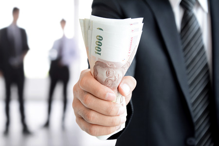 baht: Businessman hand gripping money, Thai Baht (THB) bills - investment, success and profitable business concepts