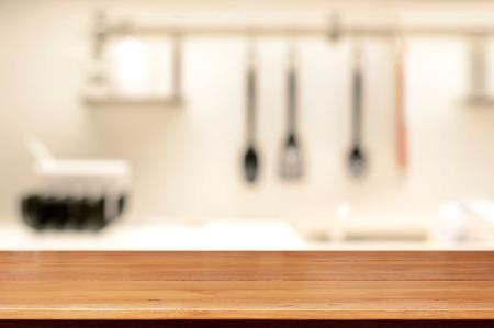 Houten tafelblad (zoals kookeiland) op onscherpte keuken achtergrond - kan worden gebruikt voor weergave of Montage uw producten Stockfoto