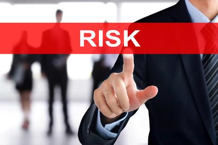 dangerous ideas: Businessman hand touching RISK sign on virtual screen Stock Photo