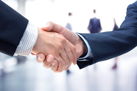 business meeting: Handshake of businessmen on blur businesspeople background - greeting, dealing,  merger and a acquisition concepts