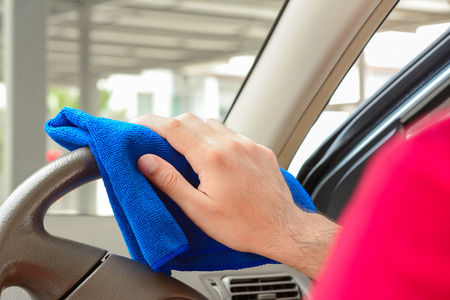 valeting: Hand cleaning car steering wheel with microfiber cloth Stock Photo