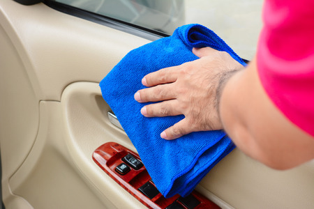clean car: Hand cleaning interior car door panel with microfiber cloth