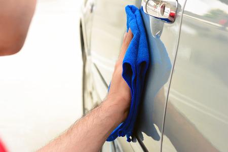 hand rubbing: A man polishing car with microfiber cloth