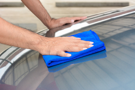 car clean: Hand polishing car bonnet with microfiber cloth Stock Photo