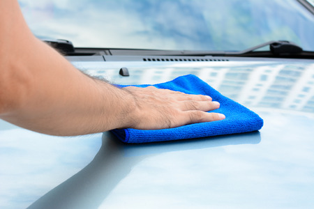 dry cleaners: Hand polishing car bonnet with microfiber cloth Stock Photo