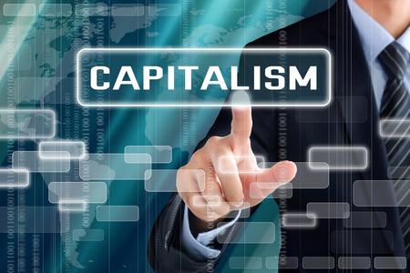 El hombre de negocios muestra de la mano tocando CAPITALISMO en la pantalla virtual