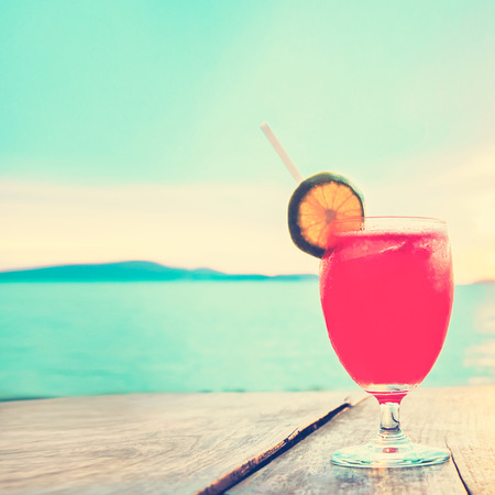 Cocktail drink on wood table in front of summer sea and sky background, vintage tone - chill out and summer holiday concept Stock Photo