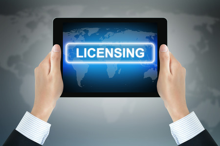 information technology law: LICENSING sign on tablet pc screen held by businessman hands