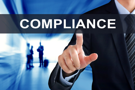 compliant: Businessman hands touching COMPLIANCE tab on virtual screen