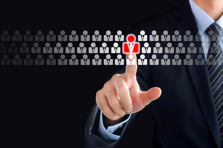 Businessman hand touching red human icon on virtual screen - stand out from the crowd, HR and HRM concepts