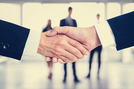 merger: Handshake of businessmen on blur businesspeople background, vintage tone - greeting, dealing, merger and a acquisition concepts