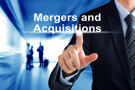takeover: Businessman hand touching Mergers and Acquisitions text on virtual screen Stock Photo