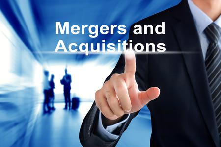 Geschäftsmann Hand berühren Mergers and Acquisitions Text auf virtuellen Bildschirm Standard-Bild