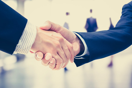 business  deal: Handshake of businessmen on blur businesspeople background, vintage tone - greeting, dealing, merger and a acquisition concepts