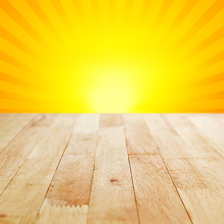 bright color: Wood table top on yellow and orange radiate (sunburst) background - can be used for display or montage your products