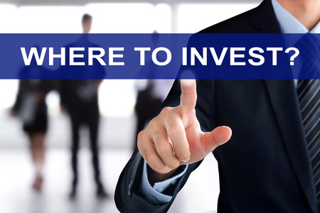 financial questions: Businessman hand touching WHERE TO INVEST? tab on virtual screen