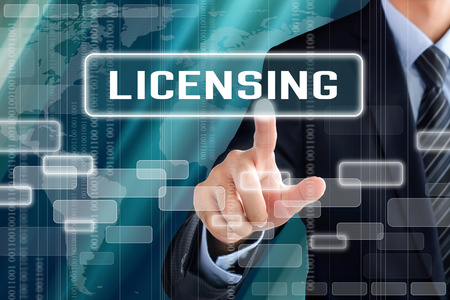 licensing: Businessman hand touching LICENSING sign on virtual screen