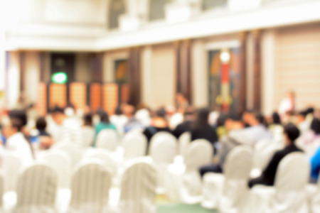 blurred people: Blurred image inside conference hall with people sitting on white chairs, back view