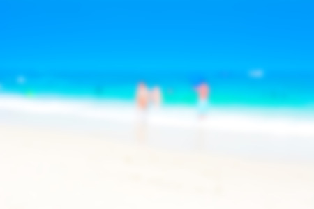 beach scene: Blurred image of white sand beach and blue sea for background