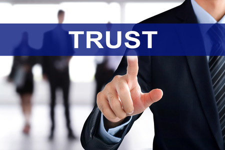trustworthiness: Businessman hand touching TRUST sign on virtual screen