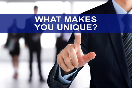 uniquely: Businessman hand touching WHAT MAKES YOU UNIQUE? text on virtual screen