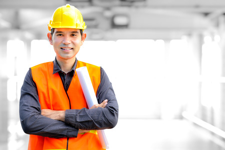 safety at work: Asian architect or engineer wearing safety vest and hard hat (or helmet) Stock Photo