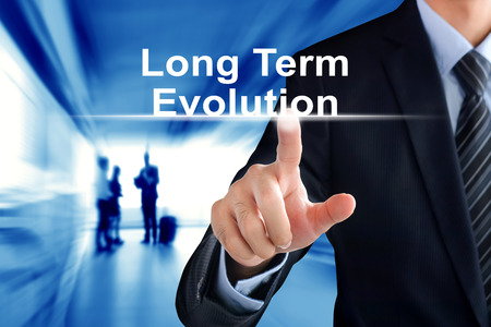 long term evolution: Businessman hand touching Long Term Evolution (or LTE) text on virtual screen Stock Photo