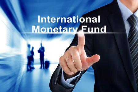 monetary: Businessman hand touching International Monetary Fund (or IMF) text on virtual screen