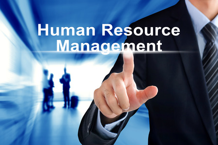 Businessman hand touching HUMAN RESOURCES MANAGEMENT (or HRM) sign on virtual screen Stock Photo