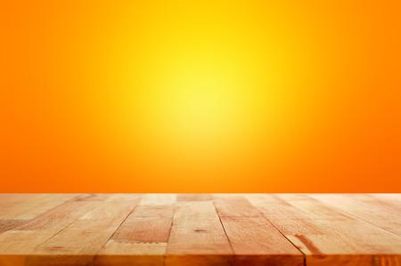 Houten tafelblad op gradiënt oranje achtergrond - kan worden gebruikt voor weergave of montering uw producten