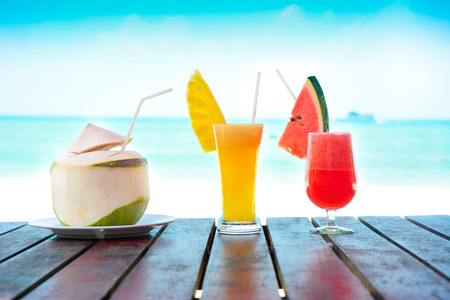slush: Colorful fruit smoothie drinks and coconut juice on the table in beach background