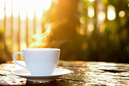 コーヒー カップの熱い太陽の下で古い木のテーブルにコーヒー ・緑の自然背景をぼかし 写真素材