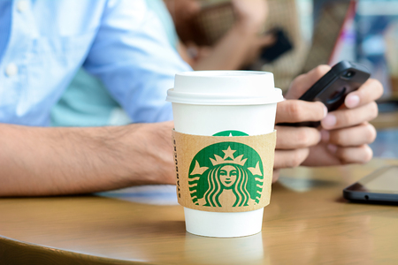 starbucks coffee: Starbucks paper coffee cup on the table with a man using smartphone as background in Starbucks coffee shop. Editorial